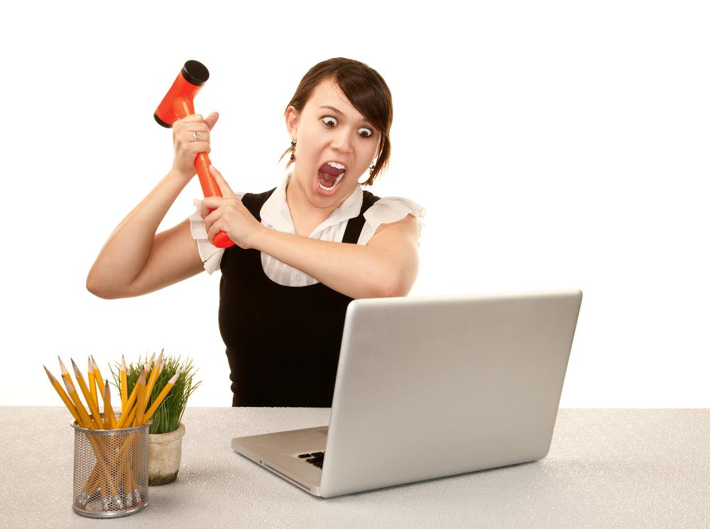 woman with hammer about to smash computer